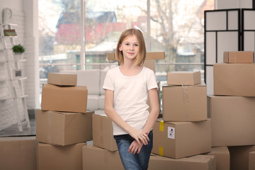Teenage girl standing near carton boxes in new house