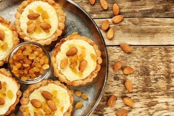 Metal tray with delicious crispy tarts on wooden table