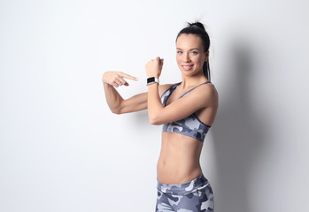 Sporty young woman with fitness tracker on light background