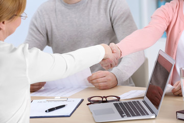 Women shaking hands sitting at workplace in light office