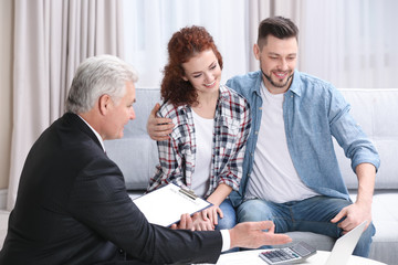 Young couple signing contract sitting on couch at home