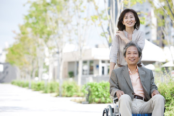 Mature woman pushing senior man on wheelchair