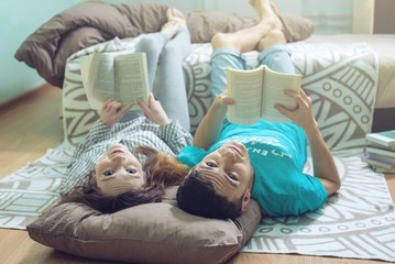 Couple lying on the floor and lifting legs nice reading