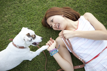 Young woman shaking hands with a dog