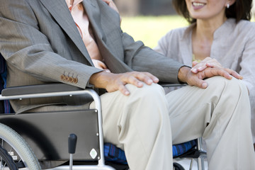 Mature woman and senior man on wheelchair holding hands
