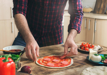 Wall Mural - Man prepares homemade pizza on a wooden table