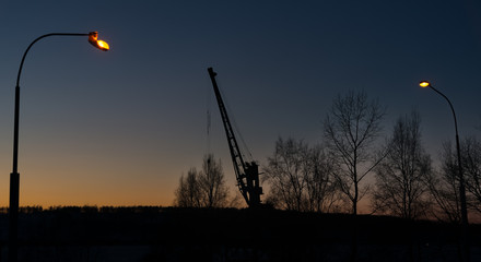 Silhouette of a port crane at sunset between two street lights