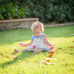 Portrait of cute happy baby girl on green glade, summer, park