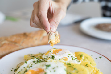 woman hand with piece of bread dipping in fried yolk egg of typical Spanish food, with sliced fried potatoes, and chopped parsley