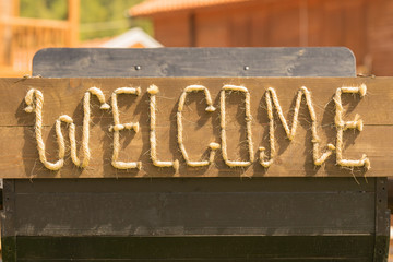 Welcome message made of ropes outside of a saloon.