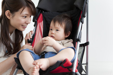 Mother Smiling at Baby Boy in Buggy