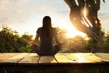 Woman practicing meditation yoga on the nature at sunset