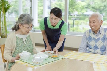 Nurse Serving Food to Senior Woman