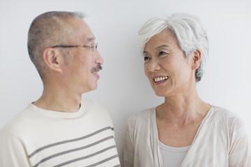 Mature couple smiling, white background