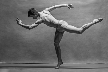 The male ballet dancer posing over gray background