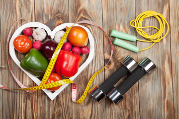 Sport and diet. Vegetables, dumbbells  centimeter. Peppers, tomatoes, garlic, onions,  radishes in the heart on rustic background