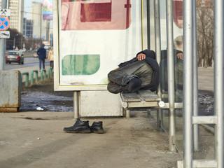 Real beggar sleeping on bus stop