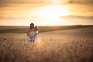 Sisters girls walk in the field with rye sunset