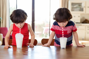 twin brothers blowing bubbles in their glass of milk