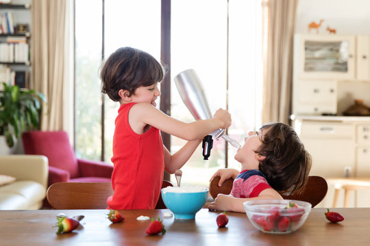 Smiling child pours whipped cream in his brother's mouth with a dispenser