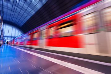 Bahnhof mit vorbeifahrendem Zug