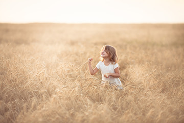 Funny girl dances in field with rye at sunset