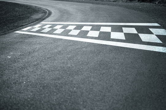 Sunny finish and start line pattern on the winding asphalt race road.