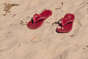 Red flip-flops on sand