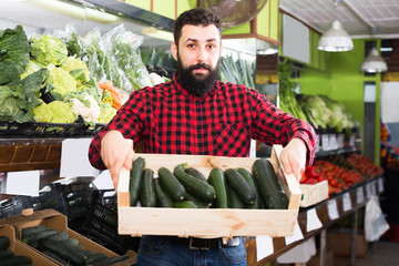 Adult male seller offering zucchinis in shop