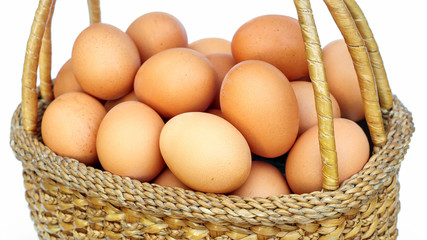 chicken eggs in a basket on white background.