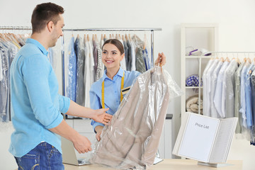 Woman working with customer in dry-cleaning salon