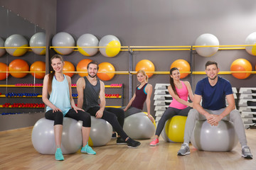 Young sporty people sitting on fit balls in gym