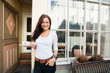 Portrait of happy young woman holding coffee cup in front of cafe