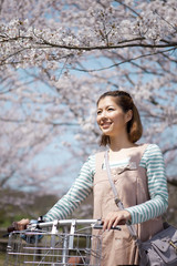 Young woman with bicycle standing near cherry trees