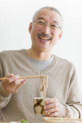 Portrait of mature man eating soba noodles, smiling, white background