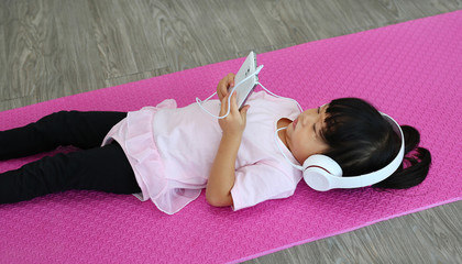 Cute little girl listening music with headphones and smartphone