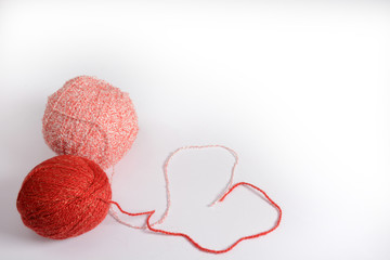 Red and pink tangle of knitting threads on a white background