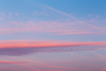 Colorful pink and blue sky with clouds. Abstract sunset background