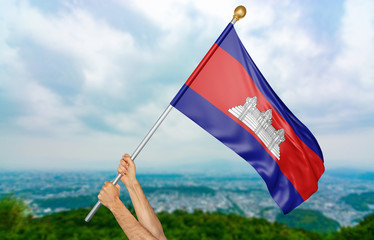 Young man's hands proudly waving the Cambodia national flag in the sky, part 3D rendering