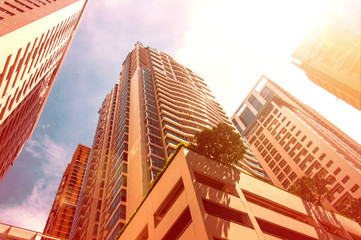 Skyscrapers at center of city with bright vivid sun glare effect and burned color effect as hot weather concept