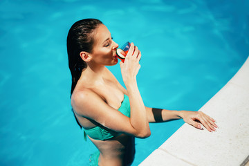 Beautiful woman drinking cocktail at pool