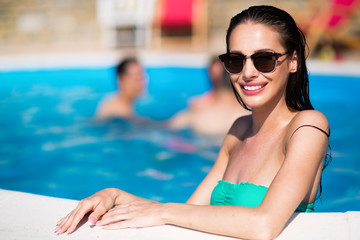 Portrait of happy woman by the swimming pool