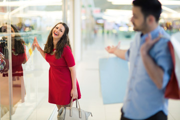 Beautiful couple enjoy shopping together in mall
