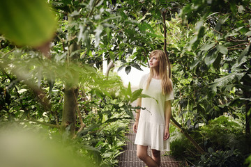 Beautiful woman in white dress amongst the plants