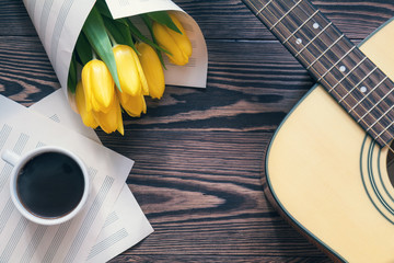 Beautiful spring background music. Guitar, yellow tulips, cup of coffee, musical page on a dark wooden background. Shallow depth of field. Coloring photo with soft focus in instagram style.