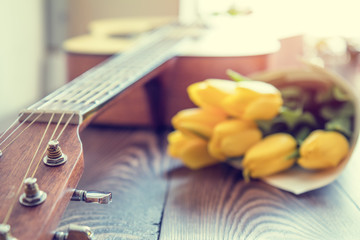 Beautiful spring background music. Guitar, yellow tulips, musical page on a dark wooden background. Shallow depth of field. Coloring and processing photo with soft focus in instagram style.
