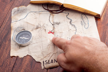Man hand point by finger into red cross on Fake treasure map of pirate island. Adventure concept background