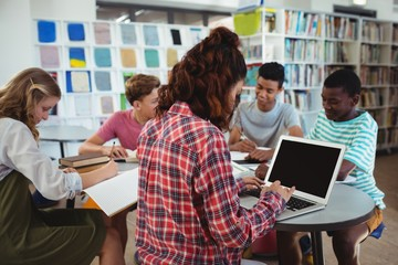 schoolgirl using laptop with her classmates