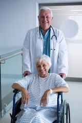 Doctor holding senior patient on wheelchair in