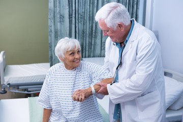 Doctor assisting senior patient at hospital